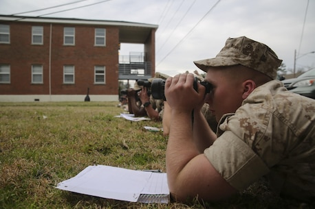 A Marine with II Marine Expeditionary Force uses binoculars to search for practice targets set by the course instructors at the Division Combat Skills Center aboard Camp Lejeune, N.C., March 9, 2015. Training to develop a better understanding of how to locate, identify and describe targets in detail is vital to Marines in the designated marksman role. Ten targets of different sizes, shapes and colors were placed in an open lot for the Marines to locate and exercise their identification skills.