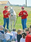 Staff Sgt. Kevin Lee (left) and Staff Sgt. Daniel Snider (right), both from the Commanding General's Mounted Color Guard, stand with one of the horses, Cyclone, at the SOAR assembly at Custer Hill Elementary School April10.