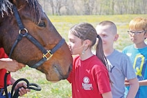 Nevaeh Lee, fourth-grader at Custer Hill Elementary School, kisses one of the horses the Commanding General's Mounted Color Guard brought to school April 10. Nevaeh's dad works with the Color Guard and she is familiar with the horses.