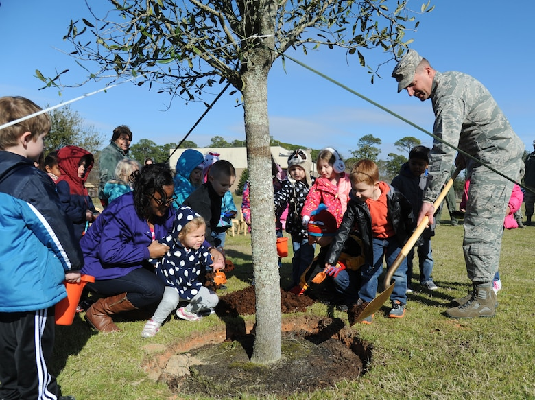 Brig. Gen. Patrick Higby, the 81st Training Wing commander, receives help from children from the child development center with planting a live oak tree outside of the CDC during an Arbor Day celebration Feb. 19, 2015, at Keesler Air Force Base, Miss. Higby, who grew up in Germany, appreciates the education and opportunities he had as a military child. (U.S. Air Force photo/Kemberly Groue)