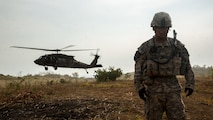 U.S. Soldier turns away from the rotor wash of the landing UH-60 Black Hawk transporting Soldiers to the landing zone during a field training exercise at Fort Magsaysay, Philippines, April 20, 2015. The training occurred during joint training exercise Balikatan 2015. Bilateral training exercises, such as Balikatan, improve the readiness of both armed forces, help maintain a high level of readiness, enhance military-to-military relations and combined combat capabilities.