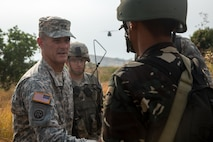 U.S. Army Maj. Gen. Charles A. Flynn, commander of the 25th Infantry Division, greets a Philippine Army Soldier assigned to the 7th Infantry Division, during a field training exercise at Fort Magsaysay, Philippines, April 20, 2015. The training occurred during joint training exercise Balikatan 2015. Bilateral training exercises, such as Balikatan, improve the readiness of both armed forces, help maintain a high level of readiness, enhance military-to-military relations and combined combat capabilities.