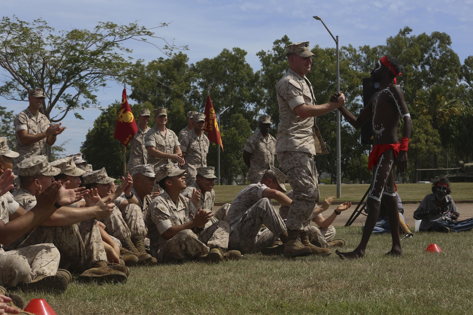 "Hospital Corpsman 2nd Class Jordan Mullan, corpsman, Combat Logistics Detachment 1, Marine Rotational Force – Darwin, is pulled out of the audience by an aboriginal dancer during a ""Welcome to Country"" ceremony  April 22 at Robertson Barracks, Palmerston, Australia. Brigadier Mick Ryan, commander, 1st Brigade, Australian Army, Australian Defence Force, spoke about the relationship between the Marines and Australians during the MRF-D deployment, and introduced Marines to aboriginal culture by inviting the Kenbi Dancers to conduct a welcoming performance. MRF-D is the deployment of U.S. Marines to Darwin and the Northern Territory, for approximately six months at a time, where they will conduct exercises and training on a rotational basis with the ADF. (U.S. Marine Corps photo by Lance Cpl. Kathryn Howard/Released)"