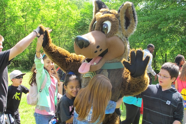 Sgt. Woof, a mascot for the Army Environmental Command, mixes and mingles with the children, emphasizing the 3Rs of unexploded ordnance safety:  Recognize, Retreat, Report.