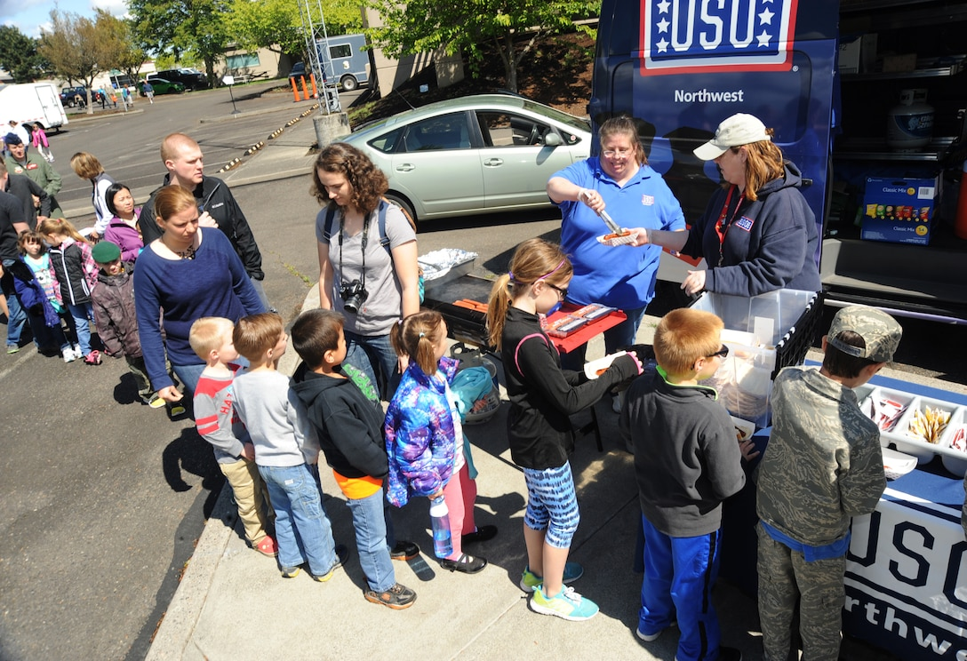 "Volunteers from the Unites States Organization (USO) Debbie McDonald and Kristie King prepare and hand out hot dogs and other snacks to kids and families attending 'Kids Day at PANG,"" April 25, 2015, Portland Air National Guard Base, Ore. The Oregon National Guard opened the Portland Air Base to children of military members for a special day of activities highlighting ""The Month of the Military Child,"" designated since 1986 by the Department of Defense as way to recognize the contribution and personal sacrifices children make to the military. (U.S. Air National Guard photo by Tech. Sgt. John Hughel, 142nd Fighter Wing Public Affairs/Released)"