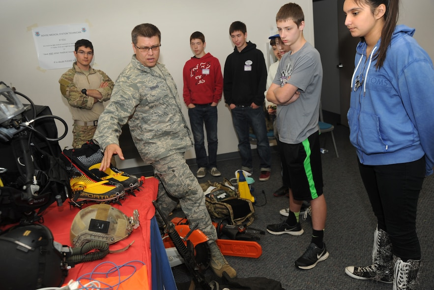 "Air Force Maj. Chris Bernard, assigned to the 304th Rescue Squadron, Portland Air National Guard Base, Ore., describes most of the gear his team use to help in search and recovery efforts to a group of teenagers attending 'Kids Day at PANG', April 25, 2015. The Oregon National Guard opened the Portland Air Base to children of military members for a special day of activities highlighting ""The Month of the Military Child,"" designated since 1986 by the Department of Defense as way to recognize the contribution and personal sacrifices children make to the military. (U.S. Air National Guard photo by Tech. Sgt. John Hughel, 142nd Fighter Wing Public Affairs/Released)"