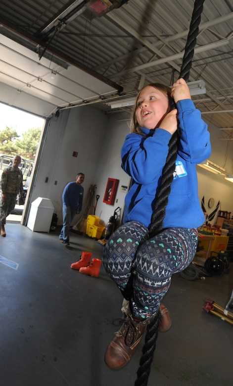 "A child attempts to climb a rope used for training by members of the Oregon Air National during 'Kids Day at PANG' April 25, 2015, Portland Air National Guard Base, Ore.  The Oregon National Guard opened the Portland Air Base to children of military members for a special day of activities highlighting ""The Month of the Military Child,"" designated since 1986 by the Department of Defense as way to recognize the contribution and personal sacrifices children make to the military. (U.S. Air National Guard photo by Tech. Sgt. John Hughel, 142nd Fighter Wing Public Affairs/Released)"