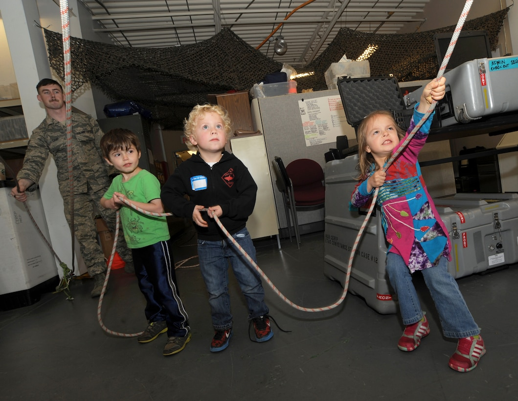 "A group of kids use a pulley system to help lift others in rescue gear while attending 'Kids Day at PANG' April 25, 2015, personnel at the Portland Air National Guard Base, Ore.  The Oregon National Guard opened the Portland Air Base to children of military members for a special day of activities highlighting ""The Month of the Military Child,"" designated since 1986 by the Department of Defense as way to recognize the contribution and personal sacrifices children make to the military. (U.S. Air National Guard photo by Tech. Sgt. John Hughel, 142nd Fighter Wing Public Affairs/Released)"