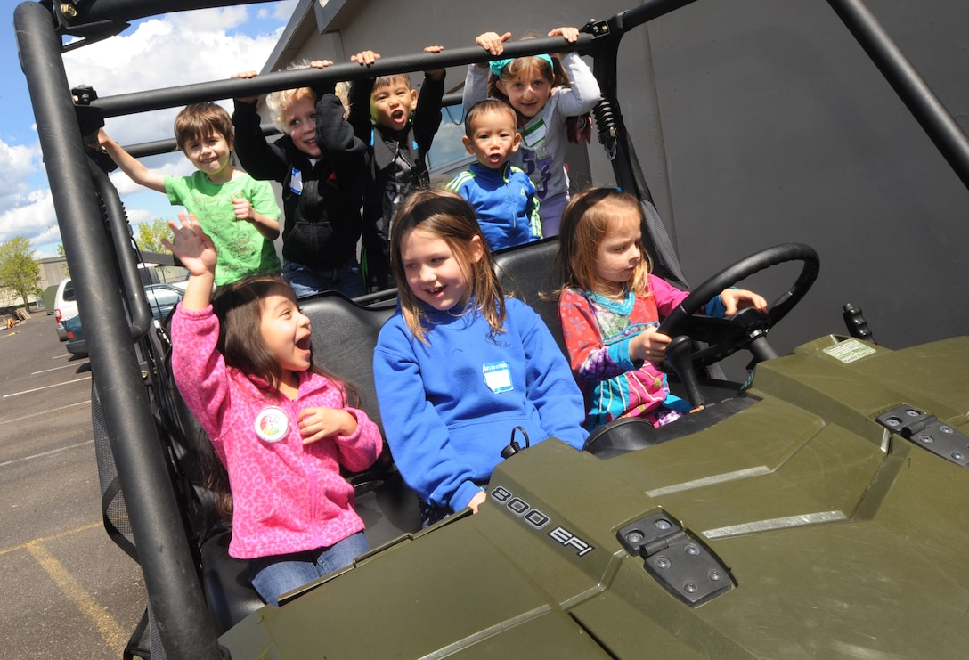 """A group of kids attending 'Kids Day at PANG' play inside one of the many vehicles used my military personnel at the Portland Air National Guard Base, Ore., April 25, 2015. The Oregon National Guard opened the Portland Air Base to children of military members for a special day of activities highlighting """"The Month of the Military Child,"""" designated since 1986 by the Department of Defense as way to recognize the contribution and personal sacrifices children make to the military. (U.S. Air National Guard photo by Tech. Sgt. John Hughel, 142nd Fighter Wing Public Affairs/Released)"""