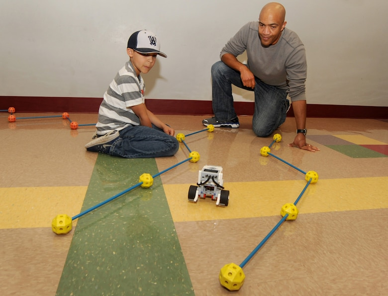 "Oregon Air National Guard Senior Airman Brain Zimmerman, assigned to Joint Forces Headquarters, Salem, Ore., helps his son Trent test a robot they have programed at STARBASE, during 'Kids Day at PANG', April 25, 2015, Portland Air National Guard Base, Ore. The Oregon National Guard opened the Portland Air Base to children of military members for a special day of activities highlighting ""The Month of the Military Child,"" designated since 1986 by the Department of Defense as way to recognize the contribution and personal sacrifices children make to the military. (U.S. Air National Guard photo by Tech. Sgt. John Hughel, 142nd Fighter Wing Public Affairs/Released)"