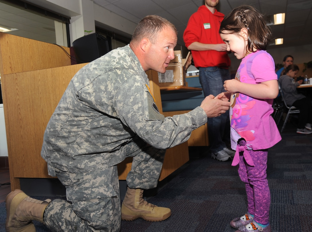 """Oregon Army National Guard Command Sgt. Major Shane Lake presents a coin to one of many children attending 'Kids Day at PANG', April 25, 2015, Portland Air National Guard Base, Ore. The Oregon National Guard opened the Portland Air Base to children of military members for a special day of activities highlighting """"The Month of the Military Child,"""" designated since 1986 by the Department of Defense as way to recognize the contribution and personal sacrifices children make to the military. (U.S. Air National Guard photo by Tech. Sgt. John Hughel, 142nd Fighter Wing Public Affairs/Released)"""