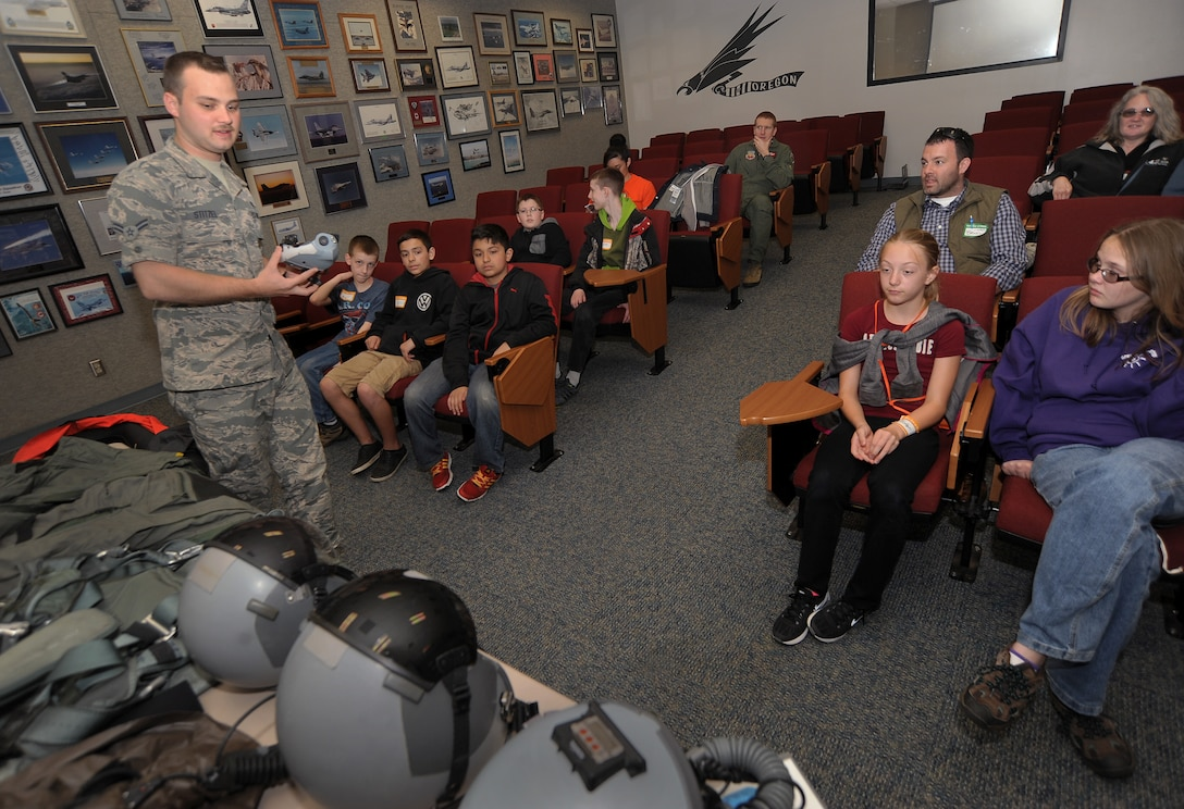 """Oregon Air National Guard Airman 1st Class Joseph Stitzel, assigned to the 123rd Fighter Squadron, 142nd Fighter Wing as an aircrew flight equipment technician, left, displays and describes some of the necessary flight gear used by Air Force pilots to some of the kids that attended, 'Kids Day at PANG,' April 25, 2015, Portland Air National Guard Base, Ore. The Oregon National Guard opened the Portland Air Base to children of military members for a special day of activities highlighting """"The Month of the Military Child,"""" designated since 1986 by the Department of Defense as way to recognize the contribution and personal sacrifices children make to the military. (U.S. Air National Guard photo by Tech. Sgt. John Hughel, 142nd Fighter Wing Public Affairs/Released)"""