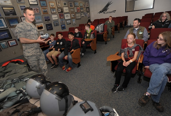 "Oregon Air National Guard Airman 1st Class Joseph Stitzel, assigned to the 123rd Fighter Squadron, 142nd Fighter Wing as an aircrew flight equipment technician, left, displays and describes some of the necessary flight gear used by Air Force pilots to some of the kids that attended, 'Kids Day at PANG,' April 25, 2015, Portland Air National Guard Base, Ore. The Oregon National Guard opened the Portland Air Base to children of military members for a special day of activities highlighting ""The Month of the Military Child,"" designated since 1986 by the Department of Defense as way to recognize the contribution and personal sacrifices children make to the military. (U.S. Air National Guard photo by Tech. Sgt. John Hughel, 142nd Fighter Wing Public Affairs/Released)"