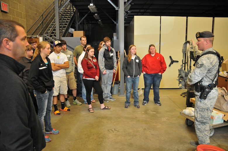 Tech. Sgt. Tyler Bassett, 114th Security Forces Squadron squad leader, shows a tactical rig to a group of high school juniors and seniors during the 2015 South Dakota Air National Guard Career Day at Joe Foss Field, S.D., April 29, 2015. The event was held to showcase the many careers the South Dakota Air National Guard has to offer to potential recruits. (National Guard photo by Staff Sgt. Luke Olson/Released)
