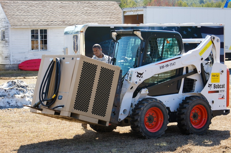 U.S. Air Force civil engineers from the 116th Civil Engineer Squadron, Georgia Air National Guard, move an environmental control unit using a Bobcat at Camp William Hinds Boy Scout Camp, Raymond, Maine, April 22, 2015. The squadron, from Robins Air Force Base, Ga., spent two weeks at the camp as part of the Innovative Readiness Training program where they are the lead unit that kicked off a project to construct a new dining facility for the Boy Scout camp. The two week deployment provided the opportunity for the squadron to get real-world training similar to the way they will be deploying in the future. The Airmen set up nine tents, installed an entire electrical grid, renovated electrical, plumbing and HVAC systems on two shower shave trailers, and worked with the duration staff to ensure materials and equipment are on site to continue the mission for future rotations. (Contributed photo/Released)