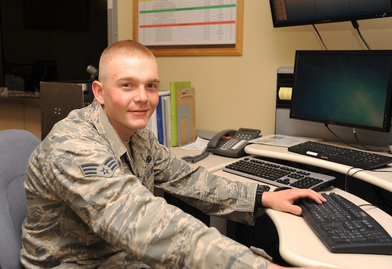 Senior Airman Sean Egan, 319th Security Forces Squadron alarm monitor, logs on to the computer to monitor live surveillance footage to detect any suspicious activity on Grand Forks Air Force Base, N.D., April 24, 2015. Egan was selected as the Warrior of the Week for the last week in April. (U.S. Air Force photo by Airman 1st Class Bonnie Grantham/Released)