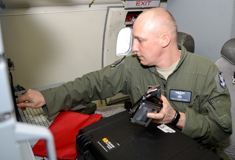 A U.S. Air Force aircrew member with the 116th Air Control Wing, Georgia Air National Guard, swaps out imagery discs during pre-flight aboard the E-8C Joint STARS aircraft for participation in the Emerald Warrior exercise, Robins Air Force Base, Ga., April 23, 2015.  During the exercise, Airmen and Soldiers from the 116th Air Control Wing and the 138th Military Intelligence Company provided real-time maritime over-watch using the one-of-a-kind battle management command and control, intelligence, surveillance and reconnaissance capabilities of the E-8C Joint STARS to joint and allied forces during a lost diver scenario. (U.S. Air National Guard photo by the 116th Air Control Wing Public Affairs/Released) (Names of aircrew members withheld for security purposes)