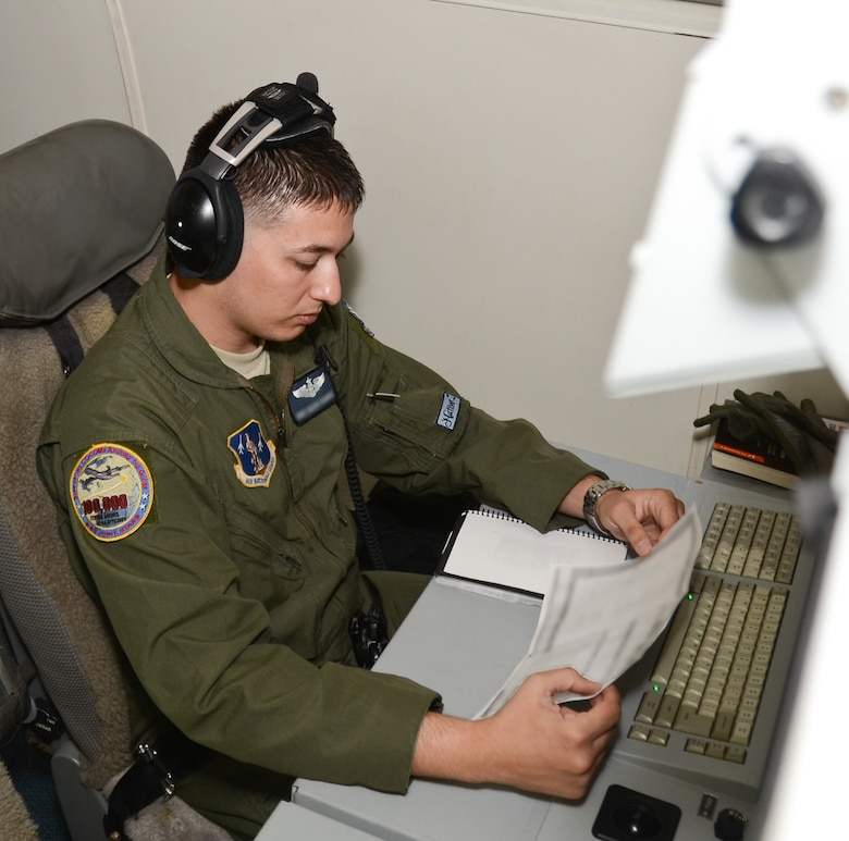 A U.S. Air Force aircrew member with the 116th Air Control Wing, Georgia Air National Guard, reviews mission information during a pre-flight aboard the E-8C Joint STARS aircraft for participation in the Emerald Warrior exercise, Robins Air Force Base, Ga., April 23, 2015.  During the exercise, Airmen and Soldiers from the 116th Air Control Wing and the 138th Military Intelligence Company provided real-time maritime over-watch using the one-of-a-kind battle management command and control, intelligence, surveillance and reconnaissance capabilities of the E-8C Joint STARS to joint and allied forces during a lost diver scenario. (U.S. Air National Guard photo by the 116th Air Control Wing Public Affairs/Released) (Names of aircrew members withheld for security purposes)