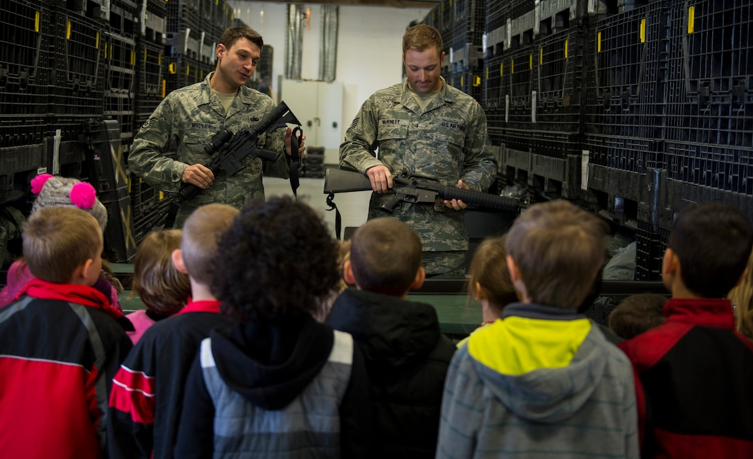 U.S. Air Force Staff Sgt. Shaun Miiller, left, and U.S. Air Force Staff Sgt. Kelley McKinley, both 52nd Logistic Readiness Squadron individual protective equipment supervisors, demonstrate weapon safety to students from Spangdahlem Elementary during Kids' Deployment Day at Spangdahlem Air Base, Germany, April 29, 2015. The students learned about the different equipment Airmen need when deploying. (U.S. Air Force photo by Airman 1st Class Luke Kitterman/Released)