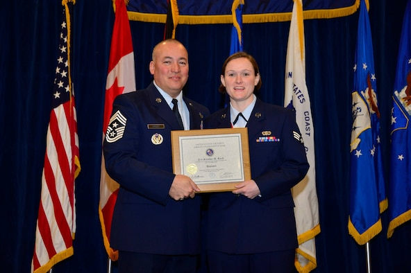 U.S. Air Force Chief Master Sgt. Mitchell Brush, senior enlisted advisor to the Chief, National Guard Bureau, recognizes Senior Airman Kristine Koch as a distinguished graduate for Airman Leadership School, 15-3. Feb. 12, 2015, at the Paul H. Lankford Enlisted PME Center, I.G. Brown Training and Education Center. (U.S. Air National Guard photo by Senior Master Sgt. Paul Mann/Released)