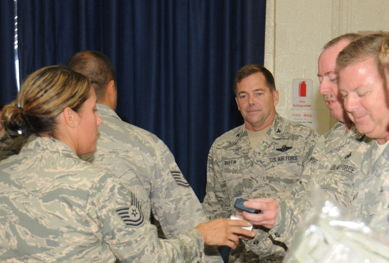 Col.William Griffin, 111th Attack Wing vice commander, watches as coins are being given to 111 ATKW members who recently re-enlisted, Aug. 1, 2015, Horsham Air Guard Station, Pennsylvania. The coins, along with other items, were formally presented by the 111th ATKW Strength Management Team during the commander's call of this month's unit training assembly. (U.S. Air National Guard photo by Tech. Sgt. Andria Allmond/Released)