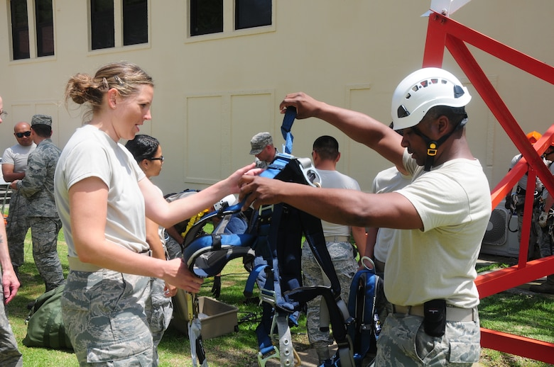 California Air National Guardsman Tech Sgt. Garrison O. Simpson, a communications technican assigned to the 129th Communications Flight, demonstrates proper use of safety gear to Airman 1st Class Kristin Blessing of the 147th Combat Communications Squadron, during a tower climbing training scenario at Lajes Air Base, Portugal, July 15, 2015. The guardsmen were tasked to decommission three towers during their one-week temporary duty assignment. (U.S. Air National Guard photo by Senior Airman Brian Jarvis)