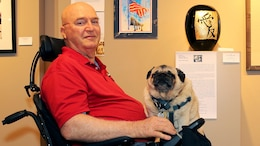 Jim Russell sits in the middle of the The Janice Griffiths Gallery at Marine Corps Base Camp Pendleton, California with his rotund service pug, Mr. Beau, resting on his lap July 24, 2015. The dim lights and cool interior of the gallery offer both some relief from the heat of the day as Russell recounts his tale of his life journey from military discipline to artistic expression.