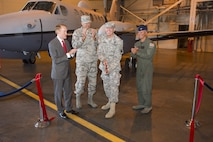 Army Maj. Gen. Robbie Asher, Oklahoma Army and Air National Guard adjutant general, cuts a ribbon during a ceremony at Will Rogers Air National Guard Base, Okla., Aug. 1, 2015. The 137th ARW celebrated the MC-12W's arrival, and is transitioning into the Air Force Special Operations Command. (Air National Guard photo by Tech. Sgt. Caroline Essex/Released)