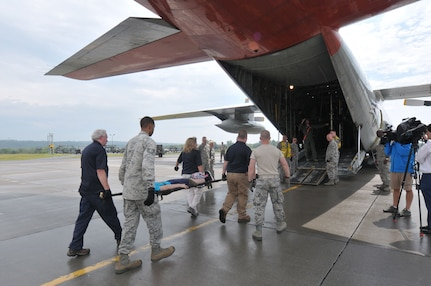 Members of the 139th Aeromedical Evacuation Squadron of the New York Air National Guard's 109th Airlift Wing, the 118th Medical Group Tennessee Air National guard and the Albany New York Veterans Administration members carry patients made up from the New York Civil Air Patrol from the staging area tent to a LC-130 Hercules aircraft during an exercise at Stratton Air National Guard Base, Scotia New York.