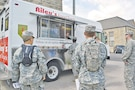 Jayme Dubbs, Riley's cook, leans down to take a Soldier's order as Tom McGee, Riley's kitchen lead, cooks the food in Riley's Food Truck on Custer Avenue.