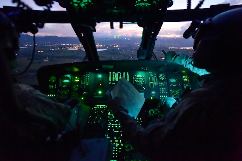 Chief Warrant Officer Craig Wenkheimer, 2-135th Aviation Battalion UH-60 Black Hawk pilot, directs 1st Lt. David Otero, 2-135th Aviation Battalion UH-60 Black Hawk pilot, during an evening training flight July 29, 2015, on Buckley Air Force Base, Colo. The 2-135th Aviation Battalion is part of the Colorado Army National Guard and has a variety of capabilities that make it a valuable resource to both the state of Colorado and the U.S. Army. (U.S. Air Force photo by Airman 1st Class Luke W. Nowakowski/Released)