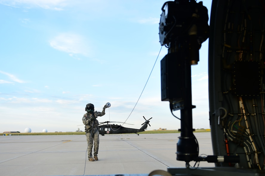 Sgt. Barbara Shirley, 2-135th Aviation Battalion crew chief, prepares the hoist before training July 29, 2015, on Buckley Air Force Base, Colo. The 2-135th Aviation Battalion is part of the Colorado Army National Guard and has a variety of capabilities that make it a valuable resource to both the state of Colorado and the U.S. Army. (U.S. Air Force photo by Airman 1st Class Luke W. Nowakowski/Released)