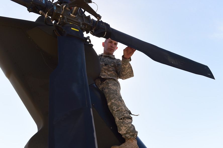 Staff Sgt. Steven Leflar, 2-135th Aviation Battalion crew chief, prepares a UH-60 Black Hawk before a flight July 29, 2015, on Buckley Air Force Base, Colo. The 2-135th Aviation Battalion is part of the Colorado Army National Guard and has a variety of capabilities that make it a valuable resource to both the state of Colorado and the U.S. Army. (U.S. Air Force photo by Airman 1st Class Luke W. Nowakowski/Released)