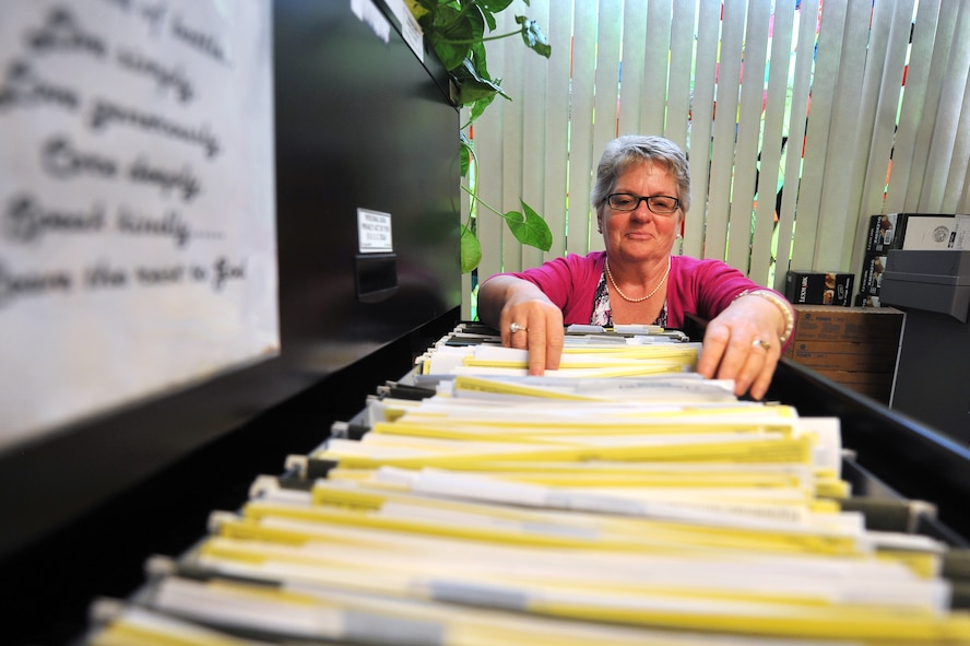 Pamela Clark, 55th Wing Judge Advocate tax representative, looks through her files July 31 at the tax center housed out of Offutt Air Force Base, Nebraska, legal office. Clark has been helping Team Offutt members with their taxes for more than a decade. (U.S. Air Force photo by Josh Plueger)