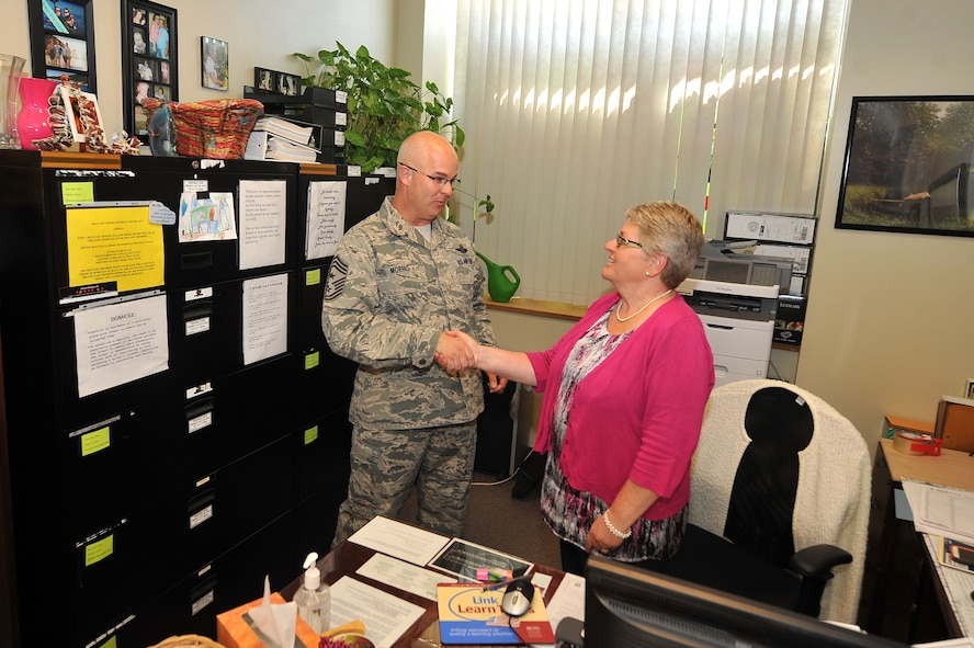 U.S. Air Force Chief Master Sgt. Michael Morris, 55th Wing command chief, coins Pamela Clark, 55th Wing Judge Advocate tax representative, July 31 at the tax center housed out of Offutt Air Force Base, Nebraska, legal office. Clark and her volunteers grossed more than $5 million in refunds last year. (U.S. Air Force photo by Josh Plueger)