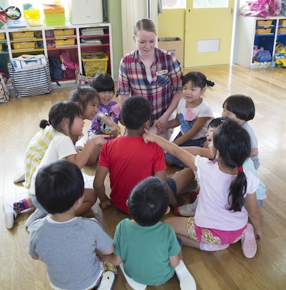 Lance Cpl. Alexa Argetsinger, a legal assistance clerk assigned to Headquarters and Headquarters Squadron, Marine Corp Air Station Iwakuni, Japan, helps students from Midoro Hoikuen School in Iwakuni City, name and locate body parts in English during a community relations visit, July 30, 2015. The Marine Memorial Chapel provides service members and their families a way to interact more closely with the Japanese and experience the culture.