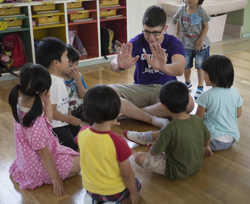 Students from Midoro Hoikuen School in Iwakuni City, Japan, listen as Lance Cpl. Justin Glandon-Hall, a broadcast journalist with American Forces Network aboard Marine Corps Air Station Iwakuni, counts to 10, July 30, 2015. Glandon-Hall is assigned to Headquarters and Headquarters Squadron, MCAS Iwakuni. Service members from the air station taught students English during a community relations (COMRELS) visit to the school. COMRELS provide an opportunity for American and Japanese cultures to be mutually shared and respected.