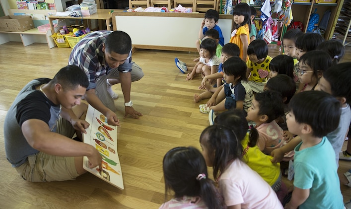 Lance Cpl. Christopher Kopack, left, and Lance Cpl. Efrain MoralesHernandez, correctional specialists with the Provost Marshal's Office aboard Marine Corps Air Station Iwakuni, Japan, read a book to students at Midoro Hoikuen School in Iwakuni City, during a community relations visit, July 30, 2015. Kopack and MoralesHernandez are assigned to Headquarters and Headquarter Squadron, MCAS Iwakuni. Volunteers played games and sang songs to help the children learn English.