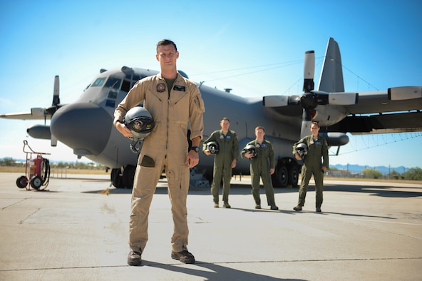 Marine Corps Capt. Jonathon Leach, a 41st Electronic Combat Squadron mission crew commander, stands with Air Force EC-130H Compass Call crewmembers on the flightline at Davis-Monthan Air Force Base, Ariz., July 31, 2015. He is part of a three-year interservice exchange program flying with Airmen from the 41st ECS. Leach is from Marine Corps Air Station Cherry Point, N.C. (U.S. Air Force photo/Airman 1st Class Cheyenne Morigeau)