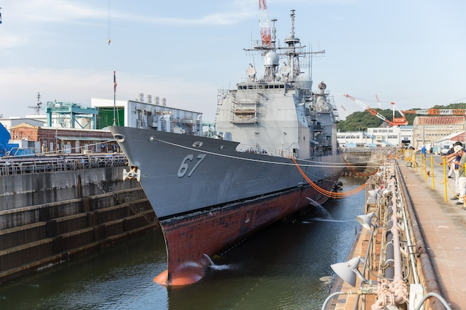 Water is drained from a dry dock as the guided-missile cruiser USS Shiloh prepares for  scheduled maintenance availability in Yokosuka, Japan, July 29, 2015.
