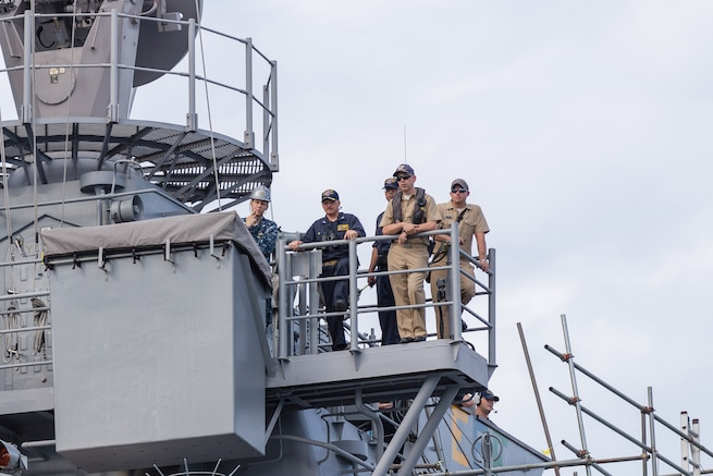 U.S. Navy Capt. Adam M. Aycock, second from left, commanding officer of the guided-missile cruiser USS Shiloh, monitors his ship's alignment as Shiloh is brought into a dry-dock for scheduled maintenance availability in Yokosuka, Japan, July 29, 2015.