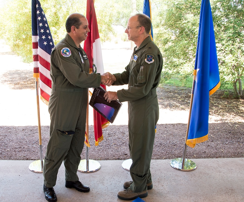 Peruvian Maj. Gen. Mario Contreras, director of the Central Hospital of the Peruvian Air Force, and U.S. Air Force Brig. Gen. Donald Lindberg, 12th AF (AFSOUTH) mobilization assistant to the commander, exchange gifts during a bar-b-que to celebrate the end of PANAMAX 2015, on Davis-Monthan AFB, Ariz., Aug. 4, 2015. The PANAMAX exercise is designed to provide interoperability training for participating multinational staffs, as well as help build-up participating nation's capability to plan and execute complex multinational operations. (U.S. Air Force photo by Staff Sgt. Adam Grant/Released)