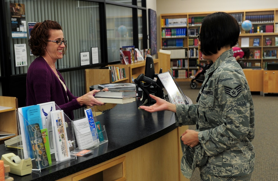 Air Force Staff Sgt. Krystal Malveaux, 509th Aircraft Maintenance Squadron weapons specialist, returns books to Anne Neudorf, 509th Force Support Squadron library aid, July 28, 2015, at Whiteman Air Force Base, Mo. For patrons ages 10 and older, library cards are freely available and can be used to check out items, as well as access the vast entirety of online resources. (U.S. Air Force photo by Airman 1st Class Jazmin Smith/Released)