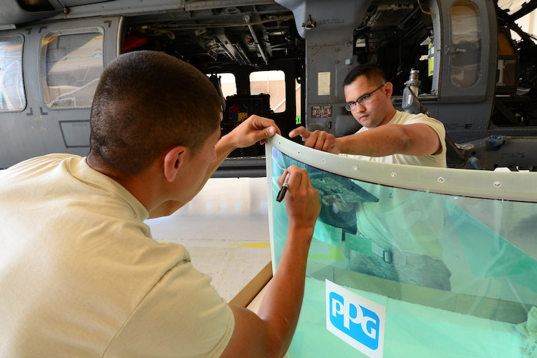 U.S California Air National Guardsmen with the 129th Rescue Wing, Moffett Federal Airfield, label a windshield for an HH-60 Pavehawk helicopter during Angel Thunder 2015 exercise at Davis-Monthan AFB, Ariz., June 2, 2015. The guardsmen are preparing the new windshield for installation. (U.S. Air National Guard photo by Senior Airman Rachael Kane/Released)