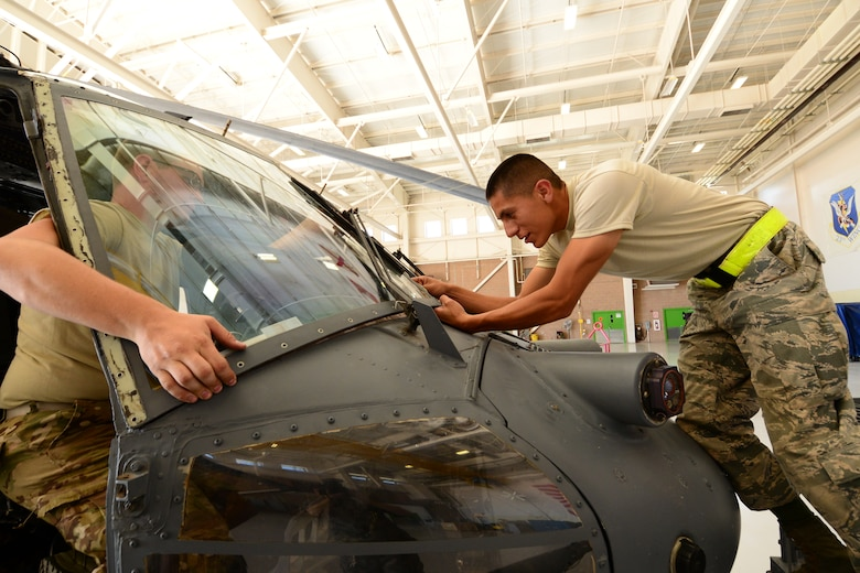 U.S. California Air National Guardsmen, Tech. Sgt. Joshua Tidwell, (left) and Senior Airman Juan Ortiz, crewchiefs with the 129th Aircraft Maintenance Squadron, Moffett Federal Airfield, Calif., remove a broken windshield from an HH-60 Pavehawk helicopter during Angel Thunder 2015 exercises at Davis-Monthan AFB, Ariz., June 2, 2015. The windshield was damaged due to flying debris. (U.S. Air National Guard photo by Senior Airman Rachael Kane/Released)