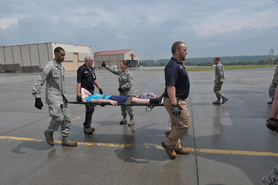 """Members of the New York Air National Guard's 139th Aeromedical Evacuation Squadron, the Tennessee Air National Guard's 118th Medical Group, and the Albany Stratton Veterans Affairs Medical Center carry """"patients"""", made up from the New York Civil Air Patrol, from the staging area tent to an LC-130 Hercules aircraft during an exercise at Stratton Air National Guard Base, Scotia, New York. The National Disaster Medical System Exercise, held July 27, 2015 through Aug. 2, 2015, demonstrated interagency partnership among the Department of Health and Human Services, the Department of Homeland Security, the Department of Defense, and the Department of Veterans Affairs and the instrumental role of aeromedical evacuation in the national emergency response and national defense frameworks. (U.S. Air National Guard photo by Master Sgt. William Gizara/Released)"""