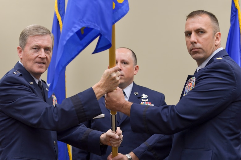 Air Force Maj. Christopher D. Gries accepts command of the 146th Air Support Operations Squadron from Air Force Maj. Gen. Gregory L. Ferguson, AFSOC mobilization assistant to the commander, August 2, 2015, Will Rogers Air National Guard Base. The 146 ASOS held a joint ceremony honoring Lt. Col. Waltermire and welcoming Air Force Maj. Christopher D. Gries as the new squardron commander. (U.S. Air National Guard photo by Tech. Sgt. Caroline Essex/Released)