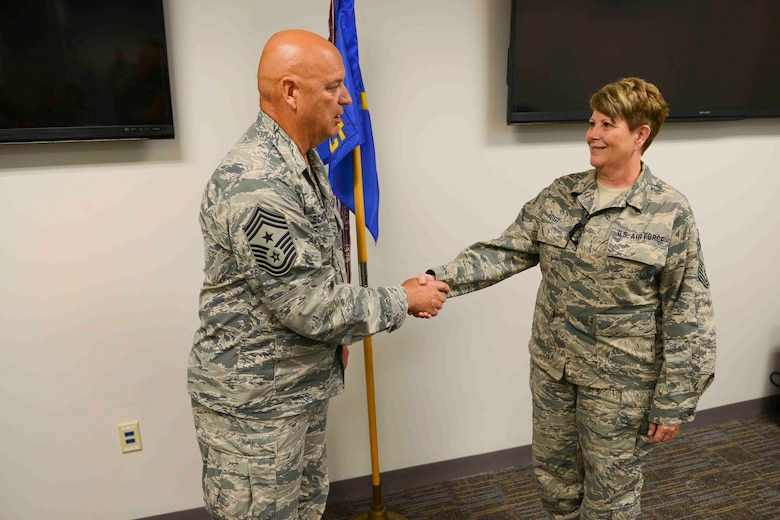 Command Chief Master Sergeant Ed Schellhase (left) presents his coin to theChief of Communications Flight, Chief Master Sergeant Michelle Yost (right) during roll call at the 132d Wing, Des Moines Iowa on Sunday, August 2, 2015.   (U.S. Air National Guard photo by Senior Airman Michael J. Kelly/Released)