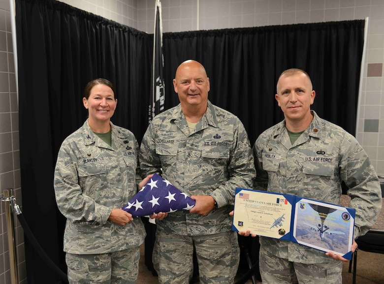 Command Chief Master Sergeant Ed Schellhase (center) receives an honorary flag from Colonel Monica Blakely (left) and Major Glen Hackley (right) at the 132d Wing in Des Moines, Iowa on Sunday August 2, 2015.  (U.S. Air National Guard photo by Senior Airman Michael J. Kelly/Released)