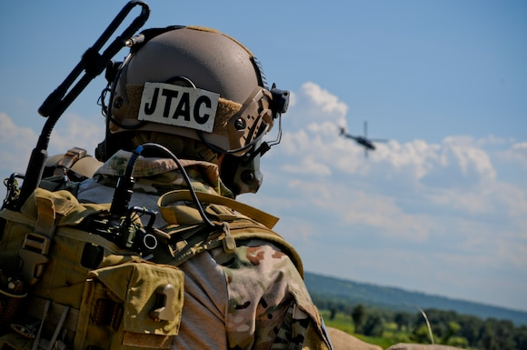 Tech. Sgt. Robert Ellis, Detachment 1 Joint Terminal Attack Controller liaison and evaluator, looks into the distance as an Army UH-60 Black Hawk helicopter performs a show of force flyover during a training simulation at Razorback Range Det. 1 Aug. 1, 2015. Ellis, along with his joint training partners in the Army and Navy, participated in a simulated training event demonstrating the unique capabilities of Razorback Range Det. 1 located at Fort Chaffee Maneuver Training Center, Ark. (U.S. Air National Guard photo by Capt. Holli Nelson/Released)